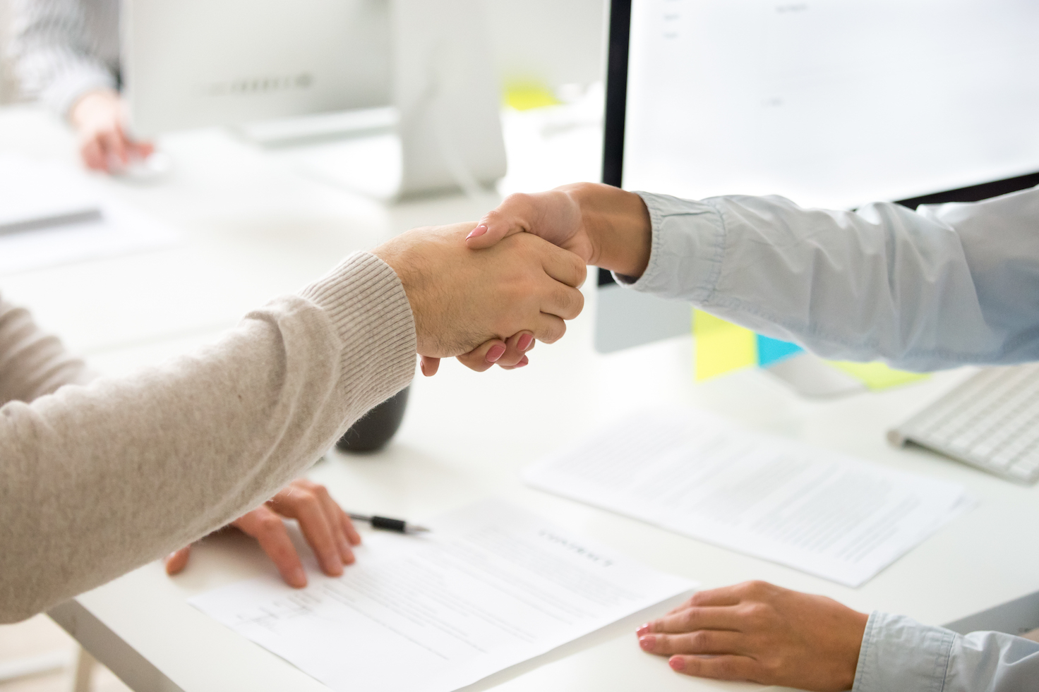 Handshake of man and woman after signing business contract, businessman and businesswoman shaking hands making employment agreement or hiring, buying insurance or becoming partners, close up view